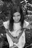 Hispanic girl crouched in garden