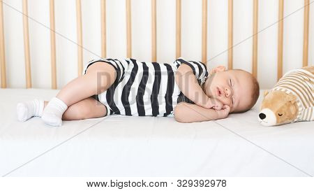 poster of Safe Sleeping For Babies. Adorable Newborn Boy Napping On His Side In Crib, Clasping Hands, Panorama