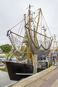 Idyllic Port Scenery Including A Shrimp Cutter Seen In Greetsiel, A Idyllic Village Located In East  poster