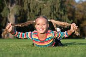 Long And Healthy From Root To Tip. Happy Small Girl Hold Long Ponytails On Green Grass. Adorable Lit poster