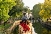 Woman Relaxing On Bridge In Strasbourg. Vacations Lifestyle. Woman Looking To River .vacation Lifest poster