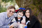stock photo of headgear  - Happy disabled boy with cerebral palsy in wheelchair surrounded by father and older sister laughing - JPG