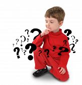 picture of curio  - A young boy is sitting down on a white background thinking with question mark symbols going around his body - JPG