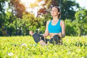 Girl Meditates In Lotus Pose On Green Grass In Park. Portrait Of Peaceful Woman With Closed Eyes. Tr poster