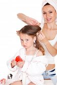 stock photo of housecoat  - Young mother styling daughter - JPG