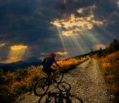 Cycling in mountain woman on cycle gravel road in autumn forest. Mountain biking in autumn landscape poster