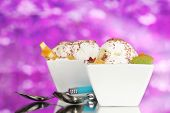delicious vanilla ice cream with chocolate and fruits in bowls and spoons on purple background