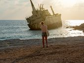 Silhouette Of Girl Taking A Photo On Sunset. Old Ship On The Mediterranean Sea Background. The Old E poster
