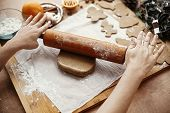 Making Christmas Gingerbread Cookies. Hands Rolling Raw Dough With Wooden Rolling Pin On Background  poster