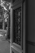 Black And White Photo Of Opened Door With Ornate Antique Grating On Door Window And Blurred Backgrou poster