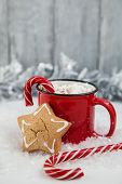 Red Mag Of Drink With Candy Cane And Christmas Gigerbread On Snowy Background. Greeting Card For Chr poster