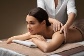 wellness, beauty and relaxation concept - beautiful young woman lying and having back massage at spa poster