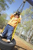 image of tire swing  - Asian child standing on tire swing - JPG