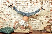 A Boy Stands Upside Down Against A Brick Wall. A Bored Boy Stands On His Head. Brick Background, Ent poster