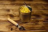 Open Tin Can Of Corn And Can Opener On Wooden Table poster