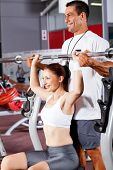 foto of personal trainer  - young fitness woman with personal trainer in gym - JPG