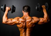 rear view of bodybuilder training with dumbbells on black background