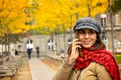 Woman Speaking On Cell Phone. Woman Speaking On Cell Phone While Walking In Park. Woman Smiling Whil poster