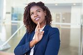 Pensive Smiling Professional Thinking Outside. Young Black Business Woman Standing At Outdoor Glass  poster