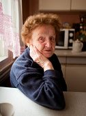 Portrait of an old woman 85 years old, in the kitchen.