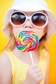 pic of cute little girl  - Adorable little girl with lollipop over colorful background - JPG