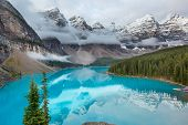 Beautiful turquoise waters of the Moraine lake with snow-covered peaks above it in Banff National Pa poster