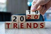 Business Man Hand Holding Wooden Cube With Flip Over Block 2019 To 2020 Trends Word On Table Backgro poster