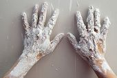 Artist plastering man hands with white dried cracked plaster texture in fingers