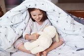 Portrait Of Cute Girl And Dog Toy Under Blanket, Little Female Kid And Dog Toy Playing Together Game poster