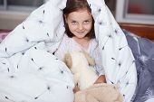 Close Up Portrait Of Little Cheerful Girl Hides Under Blanket With Fluffy Dog Toy, Sweet, Adorable C poster