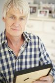 stock photo of bereavement  - Senior man with photographs at home - JPG