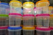 Transparent Plastic Food Containers With Multi-colored Lids Stacked In A Stack. Plastic Containers F poster