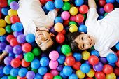 stock photo of pool ball  - Happy children playing together and having fun at kindergarten with colorful balls - JPG