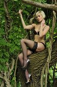 Beautiful young woman posing against a tree in the rain forest