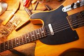 Guitar on guitar repair desk. Vintage electric guitar on a guitar repair work shop. Single cutaway e