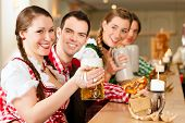 foto of stein  - Young people in traditional Bavarian Tracht in restaurant or pub with beer and steins - JPG