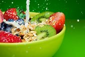 Adding Milk To Muesli With Fruits Breakfast