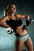 Young sports woman dumbbells exercises.