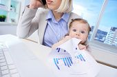 Close-up of businesswoman at workplace calling with her baby tasting document near by