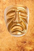 Tragedy theatrical mask on a vintage texture background