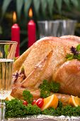 picture of christmas dinner  - Garnished roasted turkey on Christmas decorated table with candles and flutes of champagne