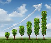 stock photo of three-dimensional-shape  - Business growth success as a financial graph shaped as growing trees with fruit and a cloud in the shape of an upward arrow as a concept of investment wealth bearing fruit - JPG