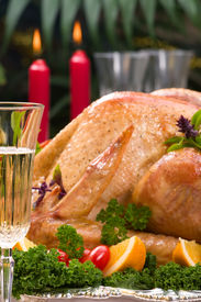 stock photo of christmas dinner  - Garnished roasted turkey on Christmas decorated table with candles and flutes of champagne  - JPG