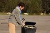 Woman Putting Rubbish In Garbage Bin