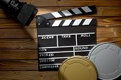 top view of clapper board with movie light and film reels on wooden table