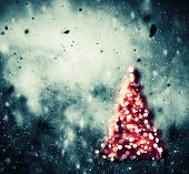Christmas tree glowing on winter background with snow storm, frost, glittering lights. Vintage texture.