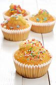 stock photo of bakeshop  - Delicious homemade muffins over white wooden board - JPG