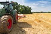 picture of plow  - Agricultural tractor ready to plow stubble fields countryside landscape - JPG