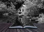 stock photo of derelict  - Creative concept pages of book Black and white retro style picture of derelict boathouse and rowing boats landscape - JPG
