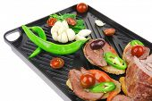 snakes on black teflon grill plate : meaty tartlets with supplements isolated over white background